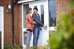 Couple at front door of new Taylor Wimpey home