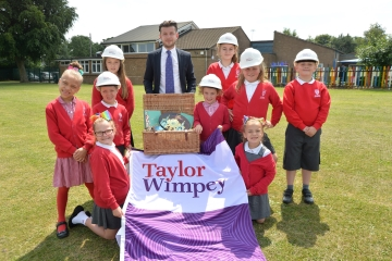 WEB  taylor Wimpey Hamper Donation  St Saviours School Children alongside Sales Executive Ashley Hol